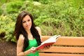 Pretty girl reading outdoors a a book on a park bench on a spring day Royalty Free Stock Photo