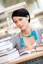 Pretty girl reads sitting at the desk woman surrounded with piles of books table reading hall academic achievement Royalty Free Stock Images