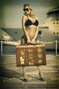 Pretty girl ready to travel waiting for the ship young blonde with bikini sunglasses and heels taking one vintage suitcase on pier Stock Photo