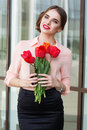 Pretty girl with red tulips and phone in hands smiling woman bouquet of her Stock Image