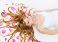 Pretty girl with rose petals in her hair Royalty Free Stock Images