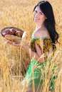 Pretty girl in rye field with basket of bread Royalty Free Stock Photo