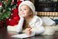 Pretty girl in Santa hat writes letter to Santa Royalty Free Stock Photo