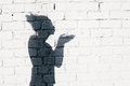 Pretty girl sending an air kiss around on the brick wall background photo of shadows of woman Royalty Free Stock Images