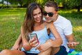 Pretty girl is showing something on smartphone to her boyfriend Royalty Free Stock Image