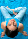 Pretty girl sitting on blue towel smiling Stock Images