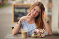 Pretty girl sitting at street cafe and drinking smoothies  on urban background. Royalty Free Stock Photo