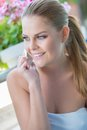 Pretty girl smiling as she chats on her phone beautiful blond sitting an outdoor patio and chatting mobile Royalty Free Stock Photography