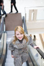 Pretty girl standing on escalator Stock Photos