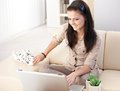 Pretty girl using laptop at home smiling Stock Image