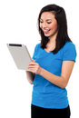 Pretty girl using tablet pc device beautiful young playing games on Stock Images