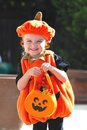 Pretty girl wearing a halloween outfit little wears pumpkin for on sunny day Stock Image
