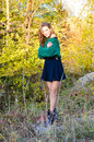 Pretty girl wearing sweater smiling on sunset picture of young woman in green and skirt standing in bushes happy in light autumn Royalty Free Stock Photography