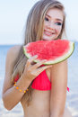 Pretty girl is wearing swimsuit eating watermelon Royalty Free Stock Photo