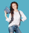 Pretty girl in a white shirt, waistcoat and hat on a blue backgr Royalty Free Stock Photo