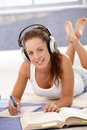 Pretty girl writing homework laying on floor learning at home using headphones smiling Royalty Free Stock Photography