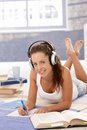 Pretty girl writing homework laying on floor learning at home using headphones smiling Stock Photo