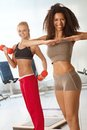 Pretty girls exercising at the gym smiling Stock Image