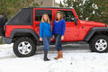 Pretty girls having fun by a Jeep Royalty Free Stock Photos