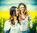 Pretty girls outdoor walking in the field in embroidery shirts Royalty Free Stock Photo