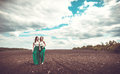 Pretty girls outdoor walking in the field, holding hands Royalty Free Stock Photo