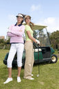 Pretty golf players with their golf cars Royalty Free Stock Images
