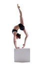 Pretty gymnast posing on cube in studio isolated over white background Royalty Free Stock Images
