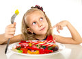 Pretty happy Caucasian female child eating dish full of candy in sweet sugar abuse dangerous diet Royalty Free Stock Photo