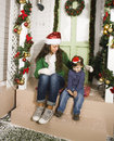 Pretty happy family sitting in front of door decorated on christmas smiling Stock Photography
