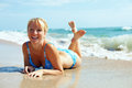 Pretty happy girl lying in surf on the beach Royalty Free Stock Images