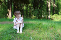 Pretty happy girl sits on green grass in forest Royalty Free Stock Photo