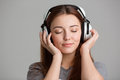 Pretty inspired young woman listening to music with eyes closed long hair over grey background Royalty Free Stock Images