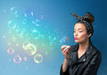 Pretty lady blowing colorful bubbles on blue background Royalty Free Stock Photo