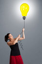 Pretty lady holding a light bulb balloon young woman Royalty Free Stock Images