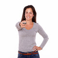 Pretty lady pointing remote control while standing Royalty Free Stock Photo