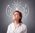 Pretty lady thinking with arrows and light bulb overhead young standing Stock Photos