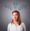 Pretty lady thinking with arrows overhead beautiful young Stock Photos