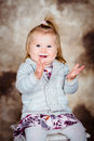 Pretty laughing little girl with blond hair sitting on chair and clapping her hands studio portrait brown grunge background Stock Photo