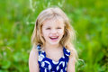 Pretty laughing little girl with long blond curly hair outdoor portrait in summer park on bright sunny day smiling child in green Royalty Free Stock Images