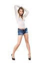 Pretty leggy blond woman wearing blue jeans shorts white blouse and black shoes isolated Royalty Free Stock Photography