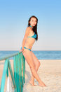 Pretty leggy brunette in blue swimsuit posing on the beach Stock Photos