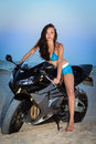 Pretty leggy brunette posing on the black motorbike Royalty Free Stock Photo