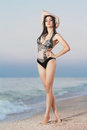 Pretty leggy brunette in swimsuit posing near the sea Stock Images