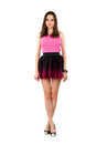 Pretty leggy woman wearing pink t shirt and short skirt isolated on white Stock Photo