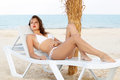Pretty leggy woman in white swimsuit lying on the beach bed Stock Photography