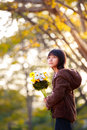Pretty little asian girl holding a bunch of flowers nature background Royalty Free Stock Images