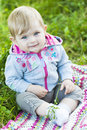 Pretty little baby portrait a cute girl sitting in the grass in the summertime Stock Image