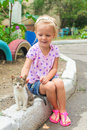 Pretty little beautiful girl plays with a homeless small kitten this image has attached release Royalty Free Stock Photography