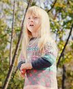 Pretty little blond girl at the forest close up with long hair wearing autumn fashion outfit woodland with tall trees background Stock Photo