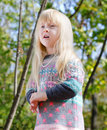 Pretty little blond girl at the forest close up with long hair wearing autumn fashion outfit woodland with tall trees background Royalty Free Stock Photo